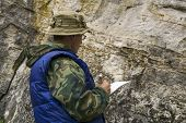 geologist conducts a description of the rocky outcrop during surface geological survey work poster