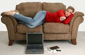 Beautiful young woman taking a break from balancing her bills online.  Laptop, cash, credit card, bills and checkbook on the floor in front of her as she relaxes on the couch watching tv. poster