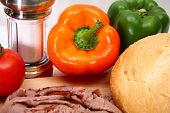 Focus on orange bell pepper surrounded by bread, roast beef and veggies. poster