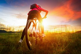 Young Woman Riding Mountain Bike On The Meadow At Sunset