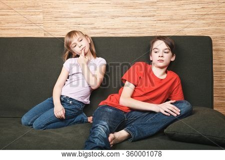 Frustrated siblings sittng on sofa stuck at home being in self-isolation. Quarantine and lockdown protective measures against spreading of coronavirus pandemic disease