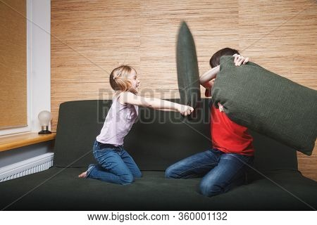Siblings going mad stuck at home being in self-isolation. Children fighting with pillows on a couch. Quarantine and lockdown protective measures against spreading of coronavirus pandemic disease