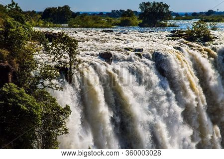 Fantastic walk after the rainy season. Grand Victoria Falls in Zambia. Victoria is a waterfall on the Zambezi River in South Africa. Concept of extreme and photo tourism