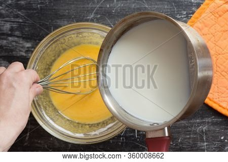 Top View Of Woman Hands Putting Hot Milk Into Mix Of Yolks, Starch And Sugar In Bowl For Making Cust