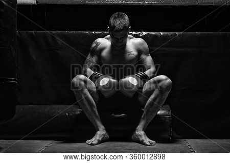 Boxer Sits In Gloves Near The Ring With His Head Bowed. The Concept Of Sports, Boxing, Mixed Martial
