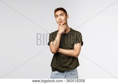 Portrait Of Young Asian Man Thinking And Looking Up With Thoughtful, Serious Expression, Rub Chin Po