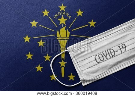 Face Medical Surgical White Mask With Covid-19 Inscription Lying On Indiana State Flag. Coronavirus