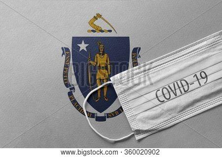 Face Medical Surgical White Mask With Covid-19 Inscription Lying On Massachusetts Flag. Coronavirus