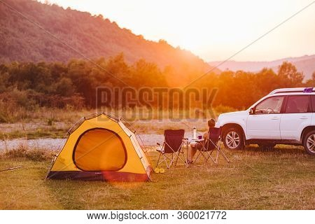 Woman Looking At Sunset Above Mountains River. Camping Concept