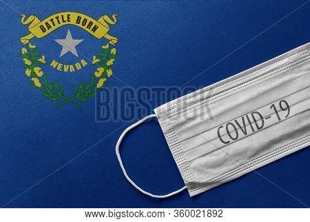 Face Medical Surgical White Mask With Covid-19 Inscription Lying On Nevada State Flag. Coronavirus I