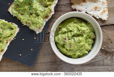 Guacamole Sauce In The Ramekin On A Wooden Surface With Toasted Tortillas On A Black Slate Plate Wit