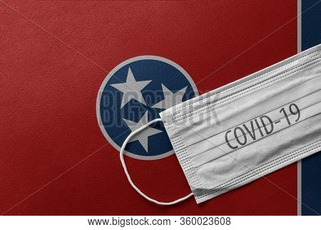 Face Medical Surgical White Mask With Covid-19 Inscription Lying On Tennessee State Flag. Coronaviru
