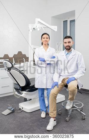 Two young contemporary dentists in gloves and whitecoats looking at you by their workplace in dental clinics with medical equipment behind