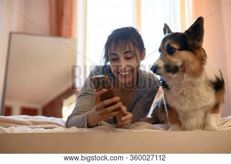 Beautiful Brunette Female Owner Lying On Bed In Bedroom With Her Cute Welsh Corgi Dog, Holding Smart