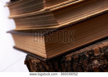 Old Books Stacked In Column. Years Of Wisdom Embodied In Encyclopedias That Today Are Overtaken By T