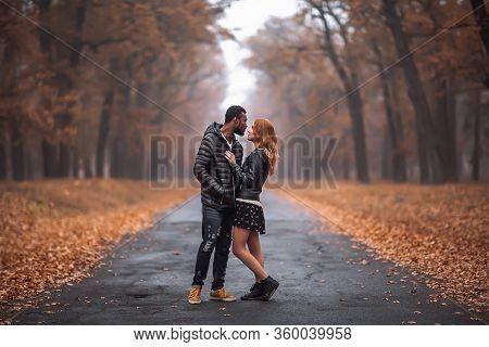 Interracial Couple Posing In Autumn Park Road