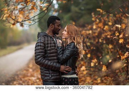 Happy Interracial Couple Posing In Blurry Autumn Park Background