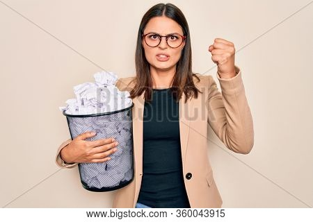 Young beautiful brunette business woman holding full paper bin of crimpled papers annoyed and frustrated shouting with anger, yelling crazy with anger and hand raised