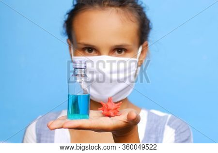 Portrait of a girl in a mask with a sanitizer and a model of coronavirus in hand.