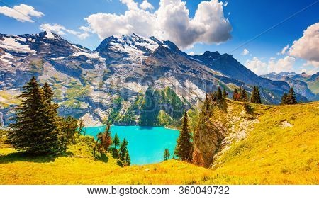 Magnificent view of the lake Oeschinensee in sunny day. Location place Swiss alps, Kandersteg district, Europe. Scenic image of unique place in world. Nature wallpapers. Discover the beauty of earth.