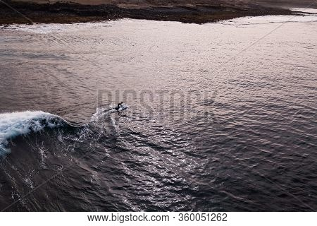 Drone View Of A Surfer Riding A Wave During Sunset Time, Aerial View Surfer Rides A Surf On A Big Wa
