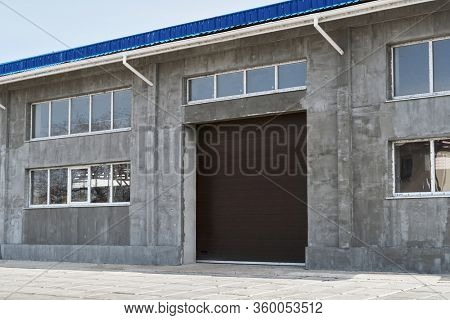 construction or renovation of a single-story building with a large gate, such as a garage or repair shop, windows and gray plaster