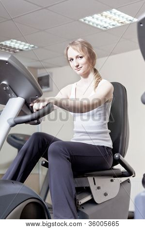 girl in a sports hall on a velosimulator