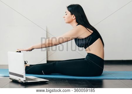Home Training, Sport, Online Fitness Class. Young Fit Woman Doing Stretching Exercise On Mat Looking