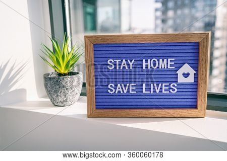 """COVID-19 Coronavirus """"STAY HOME SAVE LIVES"""" viral social media message sign with text for social distancing awareness. COVID-19 staying at home window background. Flatten the curve."""