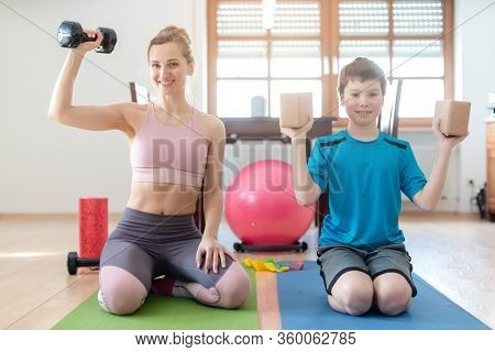 Mother and son doing weight training at home during lockdown curfew with dumbbells