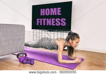 Fitness workout staying at home indoors. Asian girl doing plank exercises to exercise core watching tv videos of fit class. Young woman training muscles in front of the TV without going to the gym.