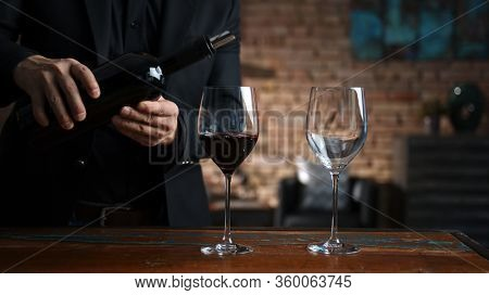 Elegant man pouring red wine from wine bottle to wine glasses at home in a cosy dark room.