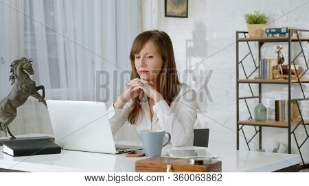 Young business woman working at desk with laptop computer in home office.