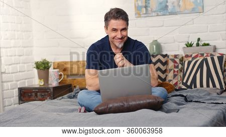 Casual man sitting on bed working online from home with laptop computer. Stay at home and work in home office.