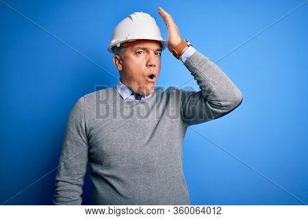 Middle age handsome grey-haired engineer man wearing safety helmet over blue background surprised with hand on head for mistake, remember error. Forgot, bad memory concept.