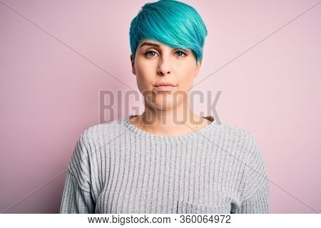 Young beautiful woman with blue fashion hair wearing casual sweater over pink background with serious expression on face. Simple and natural looking at the camera.