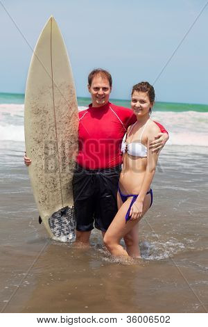 Man embraces the girl and holds surf