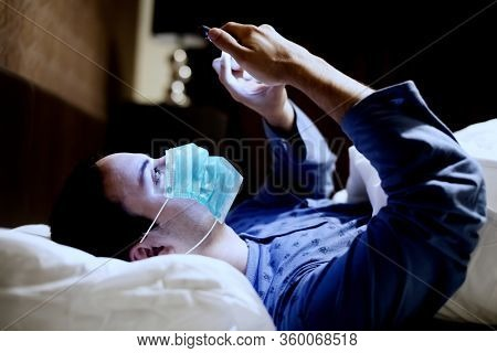 Man using his mobile phone in the bed while wearing a mask, coronavirus pandemic concept