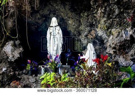Roadside Religious Statues In A Rock Outcropping With Floral And Vine Tributes.