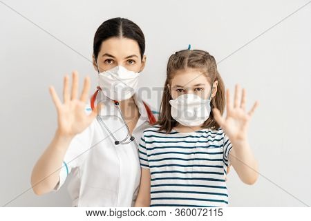 Doctor and child wearing facemasks during coronavirus and flu outbreak. Virus and illness protection, home education and quarantine. COVID-2019