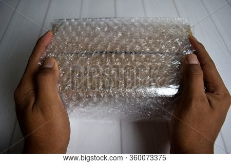 A Young Man Holding Bubble Warp And Box Inside For Protection Delivery.