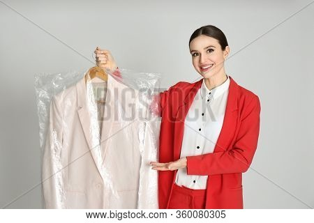 Young Woman Holding Hanger With Jacket On Light Grey Background. Dry-cleaning Service