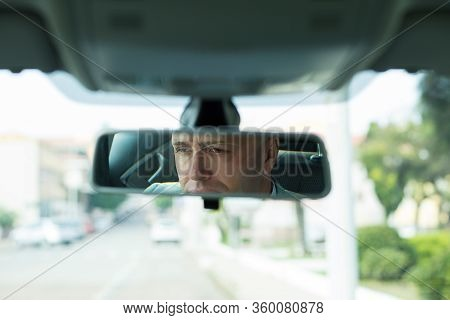 Closeup Portrait Serious Young Man Driver Reflection In Rear View Mirror Isolated Interior Car Winds