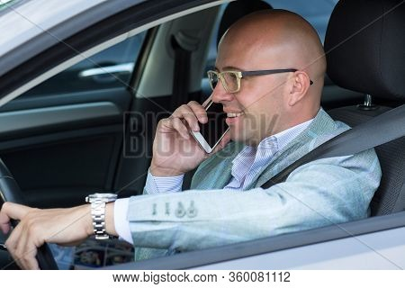 Side View Handsome Successful Young Man Smiling Talking On Mobile Phone While Driving His Car . Risk