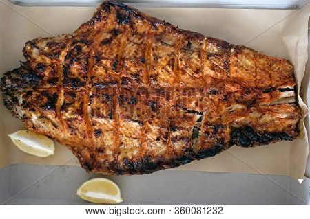 Sturgeon Filet Top View. Grilled Sturgeon Fish. Lemon Slices And Fried Fish On A Sheet Of Parchment