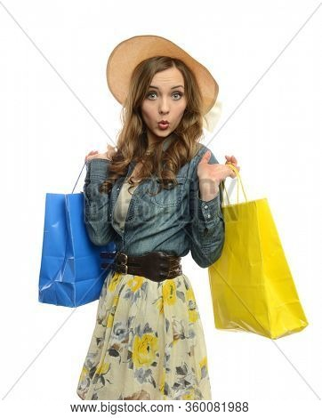 Young beautiful girl with shopping bags wearing a hat and a dress isolated on a white background