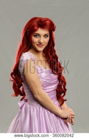 Portrait of a beaufitul redhead princess isolated on a gray background
