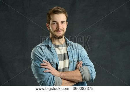 Young man cassually dressed  with arms crossed agains a gray background