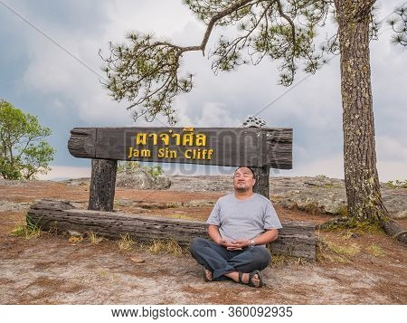 Asian Fat Trekker On Jamsin Cliff On Phu Kradueng Mountain National Park In Loei City Thailand.phu K
