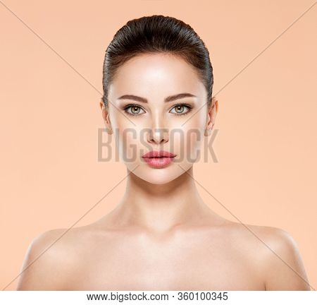 Portrait of beautiful young brunette woman with clean face. Closeup face of young adult woman with clean fresh skin. Front portrait of woman with beauty face. Beauty concept